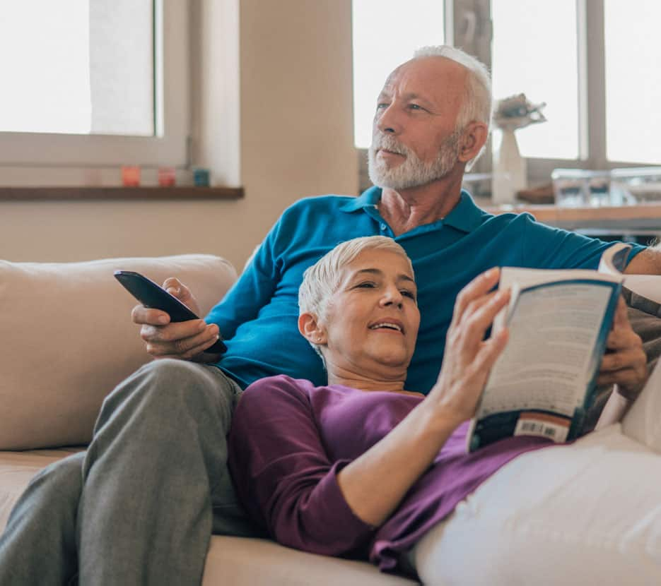 Older couple relax on the couch, man with remote, woman reading a book